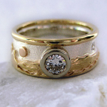Photo: Custom variation: Shoreline- Three-tone: 14k Yellow & Rose Gold, Sterling Silver, Upper rim, with 25 pt. Canadian Diamond